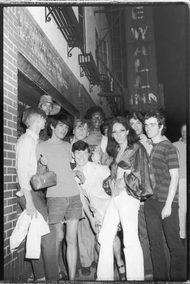 A group of young people celebrate outside the boarded-up Stonewall Inn at 53 Christopher Street after riots over the weekend of June 27, 1969.